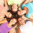 Teens lying on a sandy beach in a circle — Foto Stock