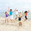 Happy crew jumping on the beach — Stock Photo