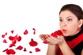 Girl blowing red petals — Stock Photo