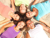 Teens lying on a sandy beach in a circle — Stock Photo