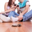 Stock Photo: Keys and young couple on the floor