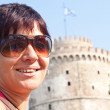 Happy tourist in front of white tower — Stock Photo