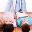 Happy couple on floor listening music — Stock Photo