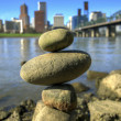 Balancing Rocks against City Skyline - Stock Photo
