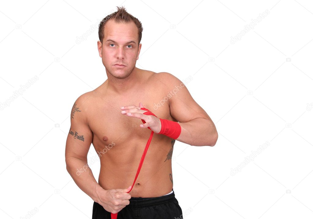 Topless boxer adult man wrapping his hands in red boxing tape before a fight — Stock Photo #1865270