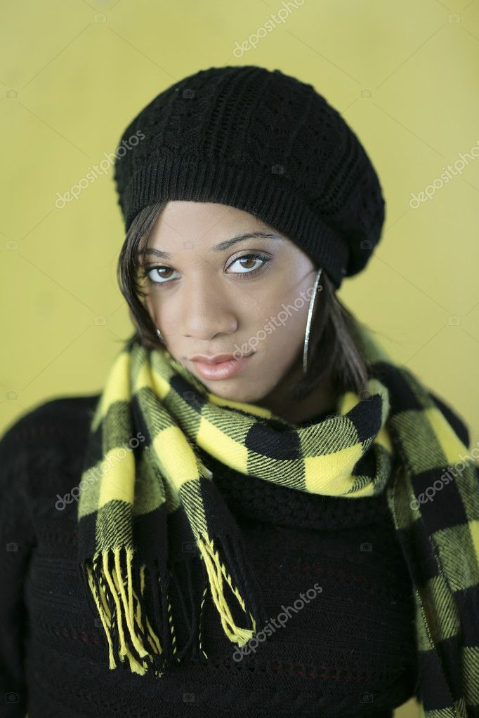 One fashionable young woman model posing over a yellow wall in cold weather garb  Stock Photo #2034595