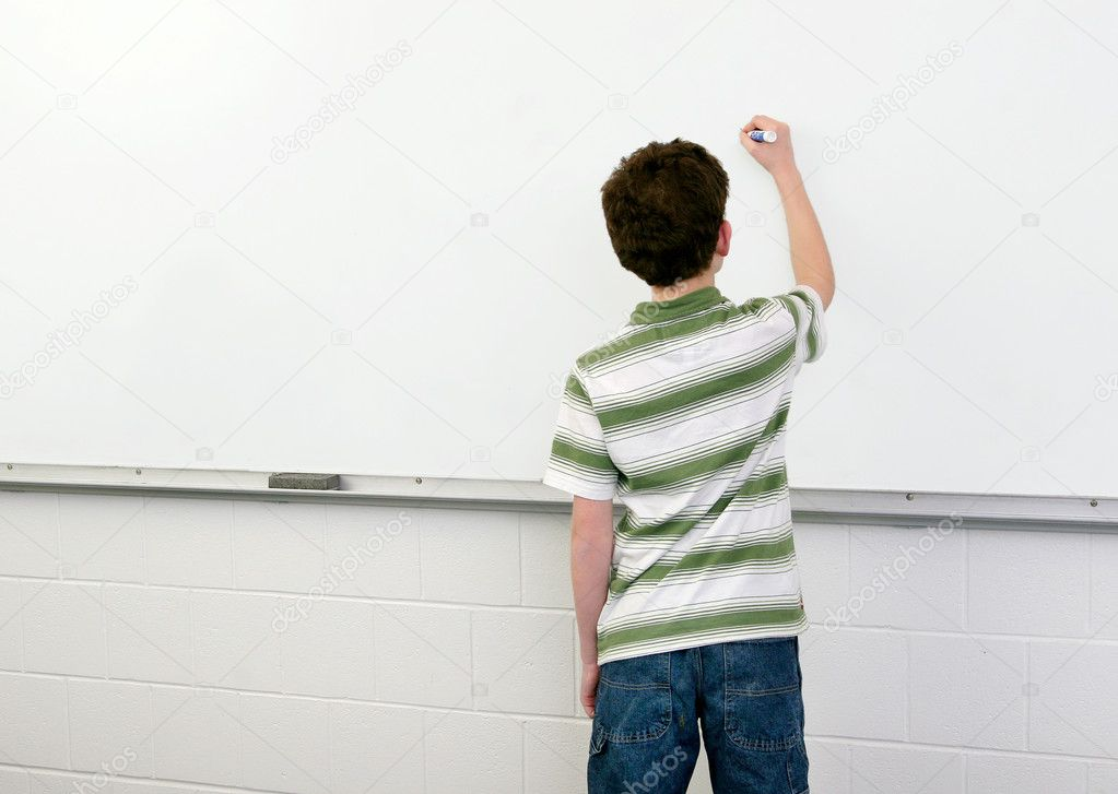One young male student in a classroom writing on a whiteboard — Stock Photo #2038712