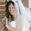 Bride on a brick wall — Stock Photo