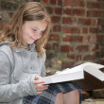 Schoolgirl reading outside — Stock Photo