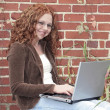 Woman on laptop outdoors — Stock Photo