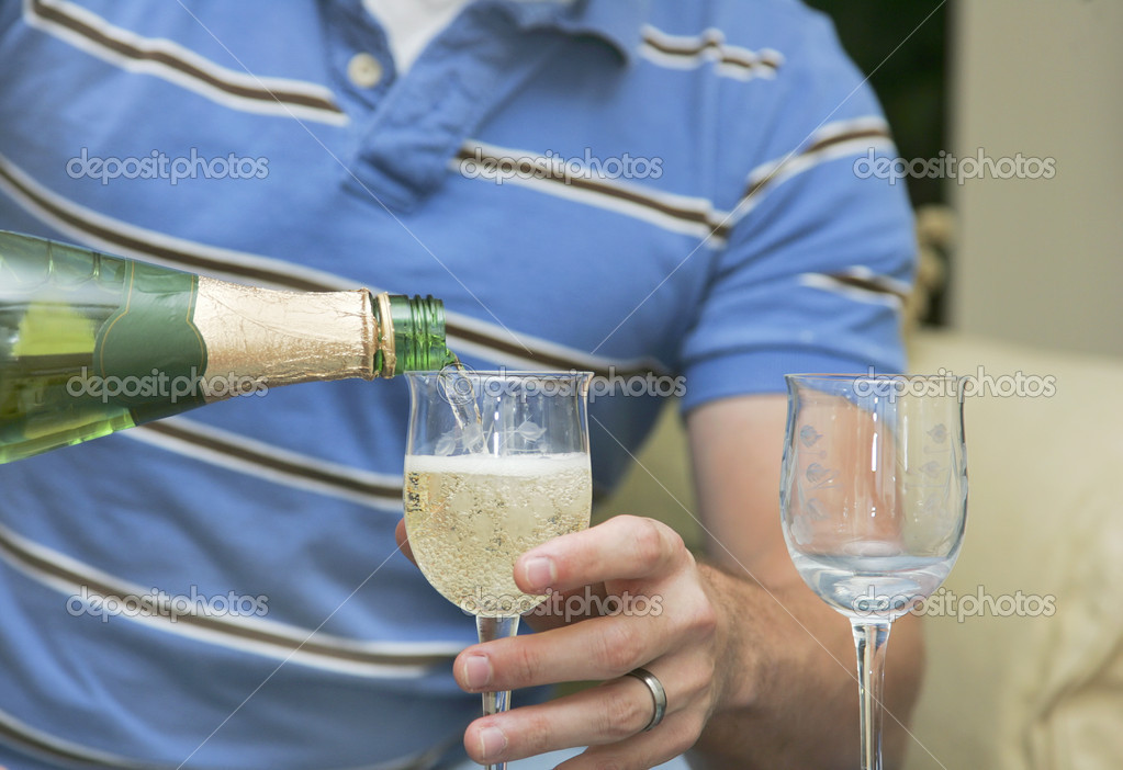 Young man holding a glass and pouring white wine to celebrate — Stock Photo #2040830