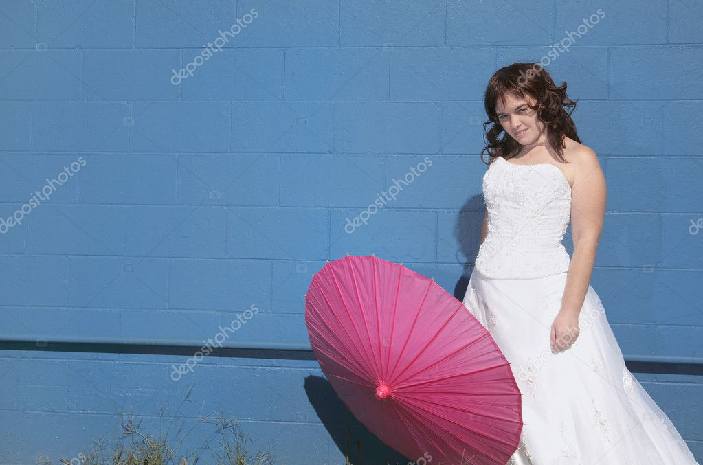 One curly haired adult female in a wedding dress with a pink parasol — Stock Photo #2042183
