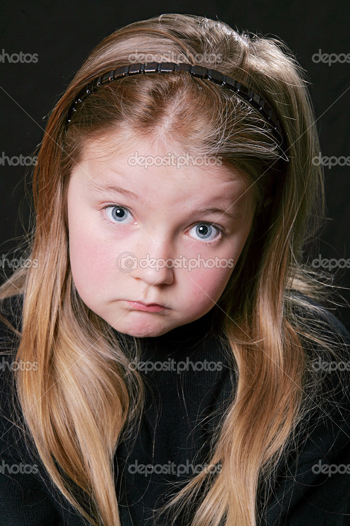 Young chlid looking upset over a black background — Stock Photo #2049283