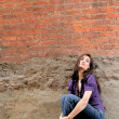 Woman sitting against a brick wall — Stock Photo