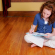 Young girl sitting on the floor writing - Stock Photo