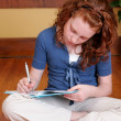 Young girl sitting on the floor writing — Stockfoto