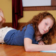 Young girl laying on the floor writing — Stock Photo #2175762