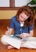 Young girl sitting on the floor writing — Foto Stock