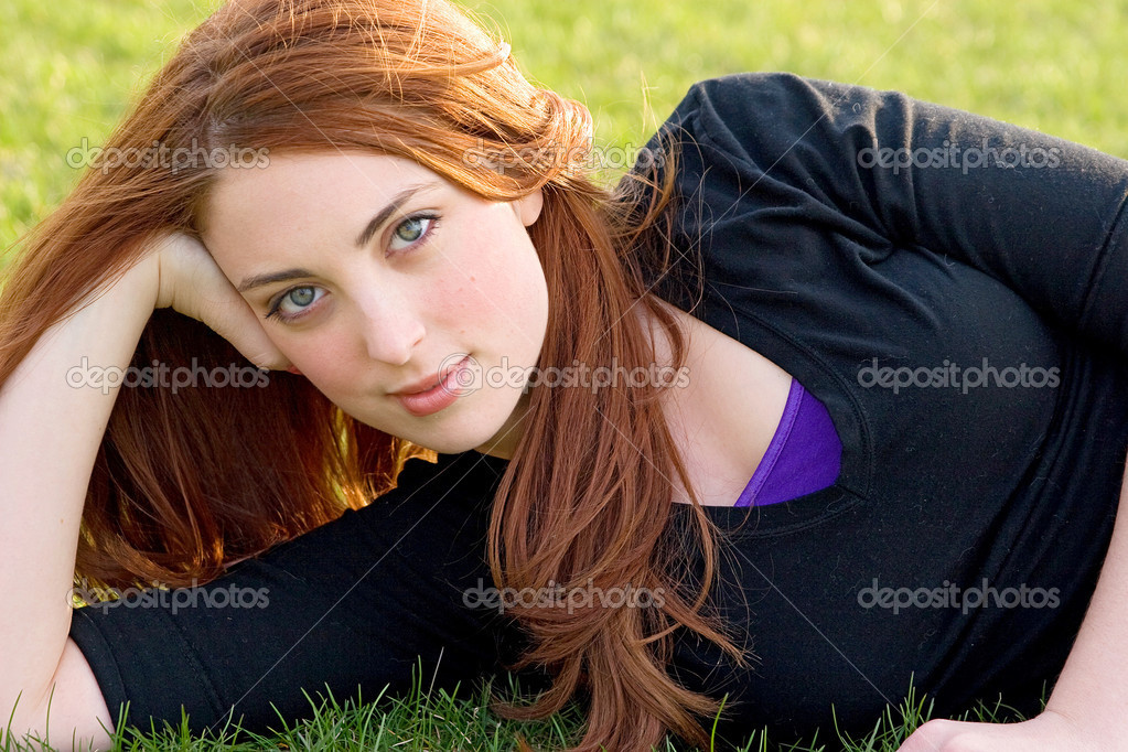 One twenties young adult redhead woman laying on the ground outdoors. ...