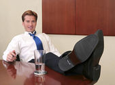 Businessman with feet up — Stock Photo
