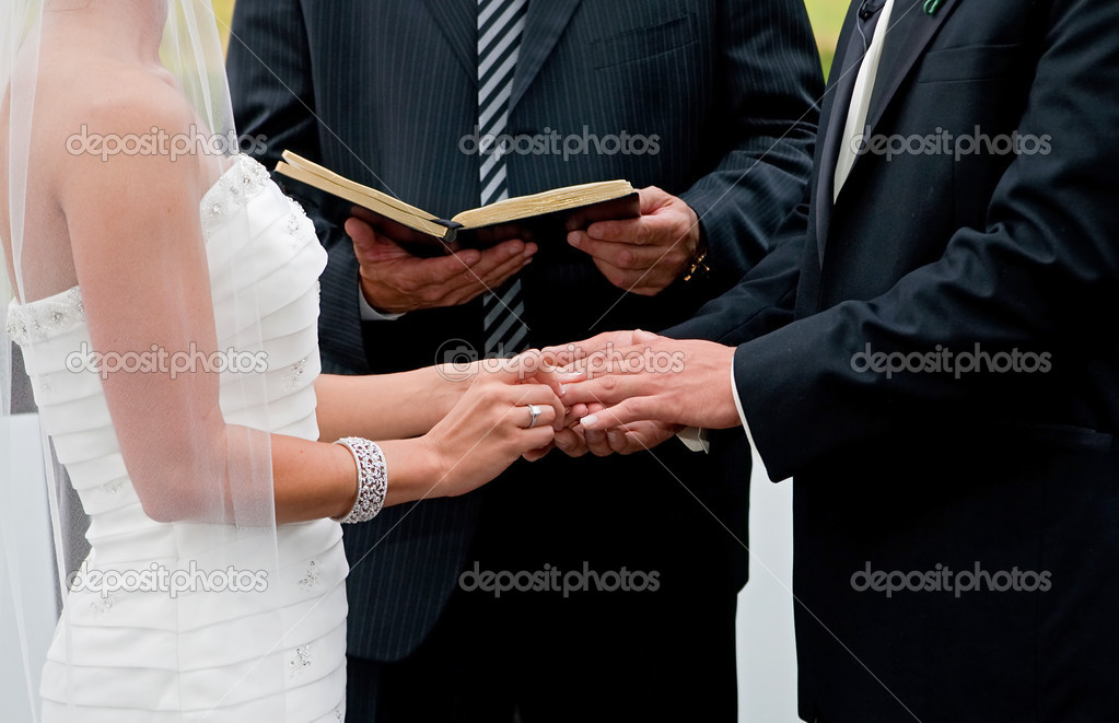 Bride and groom holding hands during ring exchange part of an outdoor wedding ceremony — Stock Photo #2573336
