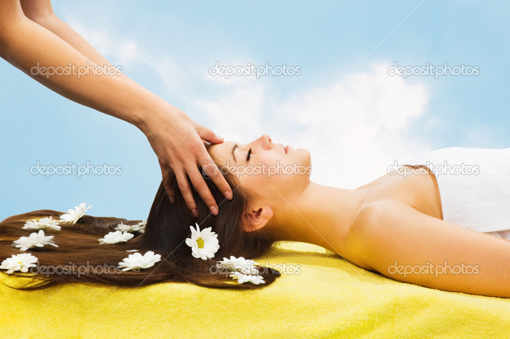Young attractive girl receiving head massage at spa resort against sky backgr — Stock Photo #1897782