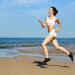 Young woman running alone on the beach — Stock Photo
