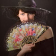Pretty woman with a fan — Stock Photo