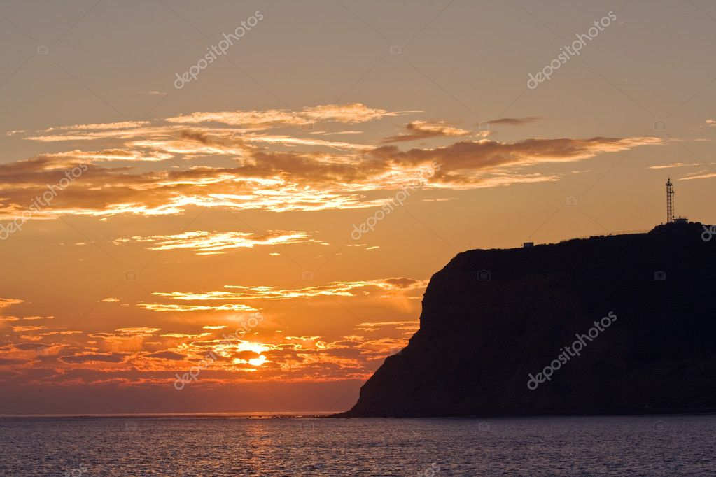 Point Loma silhouetted behind a setting sun and orange sky on the coast of California where San Diego Bay meets the Pacific Ocean  Stock Photo #1922675