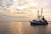 Fishing trawler on the water at sunrise — Stok fotoğraf