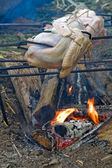 Turkeys roasting over an open fire — Stock Photo