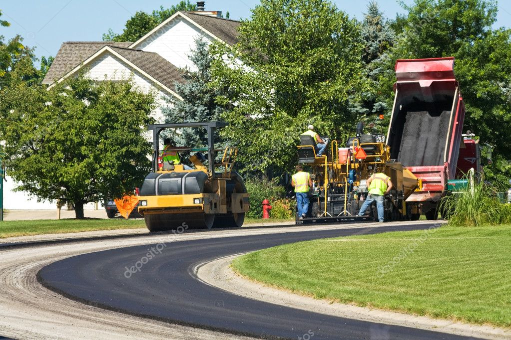 Steamroller and dump truck crews laying new pavement in a residential neighborhood — Stock Photo #2660433