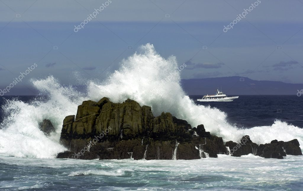 Waves breaking over a large rock in Monterey Bay while a tour boat passes in the distance off the coast of Pacific Grove, California — Stock Photo #2666006
