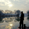 Stock Photo: Silhouette of fishing man, calm river