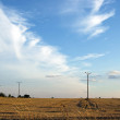 Poles on the field with clouds — Stock Photo