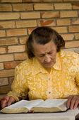 Elderly woman reading Bible — Stock Photo