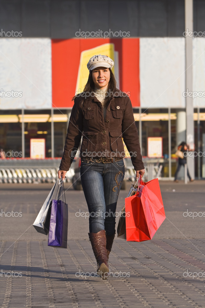 Happy young woman with shopping bags in front of a supermarket. — Stock Photo #1985426