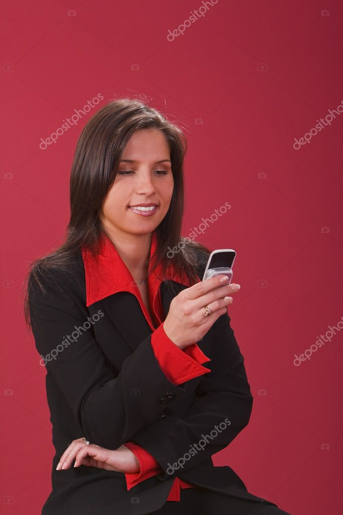 Young smiling brunette checking her mobile phone.  Stock Photo #2006327