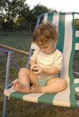 Little boy sitting in a deckchair — Stock Photo