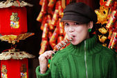 China girl eating candied fruit — Stock Photo