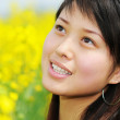 Pretty girl in rape flowers — Stock Photo