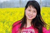 Pretty girl in rape flowers — Stock Photo