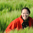 Asian woman grass in red — Stock Photo #2570336