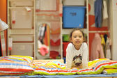 Happy little girl by bed — ストック写真
