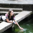 Chinese girl playing by water — Stock Photo