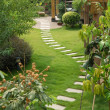 A stone walkway winding its way through a tranquil garden  — Stock Photo