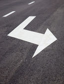 Road signs arrows on asphalted surface — Stock Photo