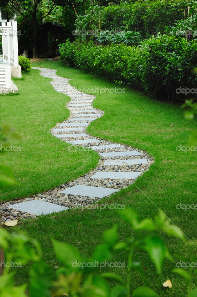 Garden stone path with grass growing up between the stones — Stock Photo #1879939