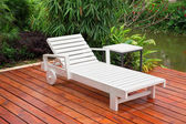 Wooden reclining chair in a garden — Stok fotoğraf