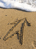 Arrow on wet sea sand — Stock Photo